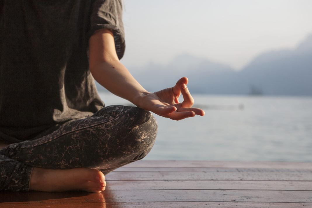 kobieta praktykująca jogę nad jeziorem