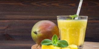 mango-smoothie-ze-słomy-i-mięty-w-zlewce-szklanej-płyta-z-pokrojonymi-mango
