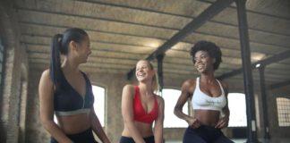 trzy kobiety w sportowych strojach śmieją się do siebie