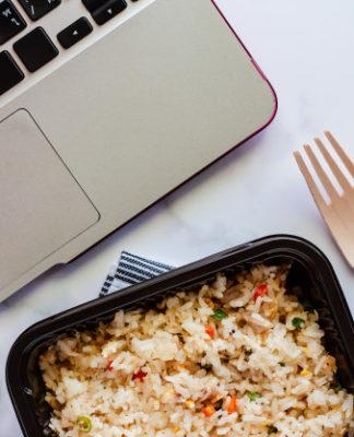 wyśmienicie-smażący-ryż-w-lunchu-pudełku-na-napery-z-drewnianą-łyżką-rozwidlenie-i-komputerowy-laptop-przy-miejscem-pracy