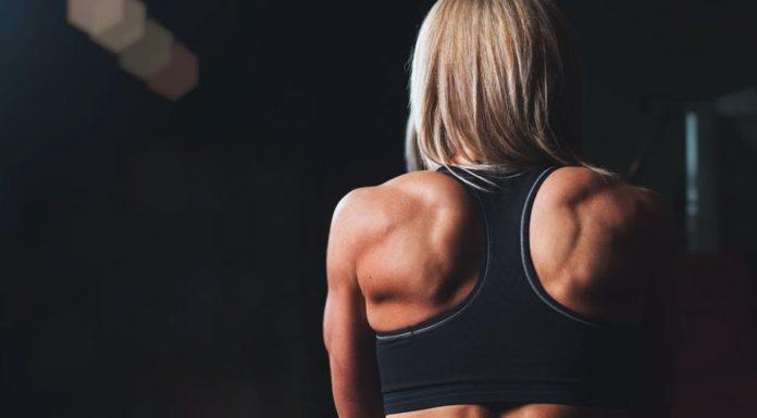 wysportowana dziewczyna blondynka w czarnym topie stojąca tyłem