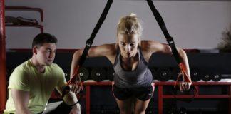 kobieta ćwiczy na siłowni z trenerem