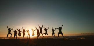 dorośli skaczą przy zachodzie słońca