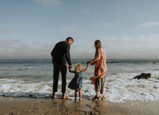 rodzice z dzieckiem nad brzegiem oceanu