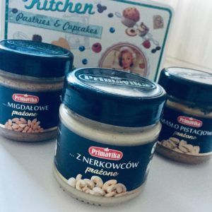 three kinds of peanut butter, cashews butter in front of and on the background almonds butter and pistachio butter