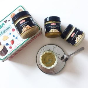 three kinds of peanut butter, almonds butter, pistachio butter, cashews butter on a table with little spoon and empty jar of the peanut butter