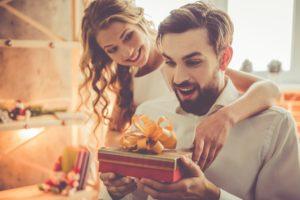 kobieta brunetka wręcza mężczyźni prezent owinięty w papier ze złotą kokardą