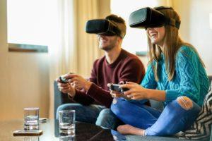kobieta i mężczyzna siedzą na kanapie i grają w okularach VR